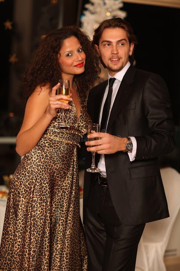 Pares jovenes felices con los vidrios del champán imagen de archivo libre de regalías