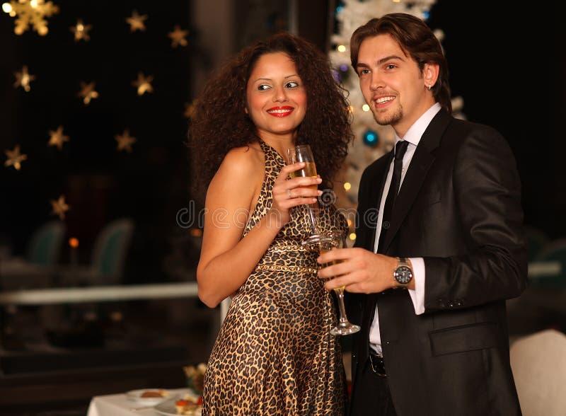 Pares jovenes felices con los vidrios del champán fotos de archivo libres de regalías