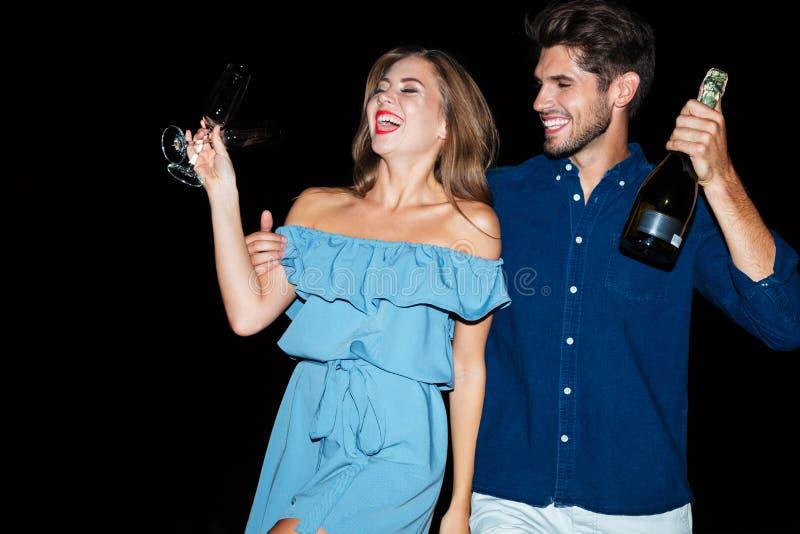 Pares jovenes felices con los vidrios y la botella de champán foto de archivo libre de regalías