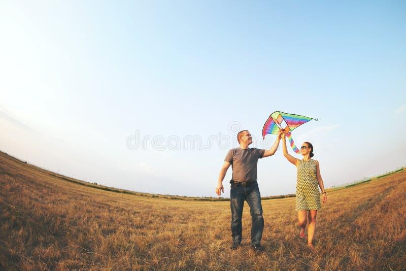 Pares jovenes felices con volar una cometa imagenes de archivo