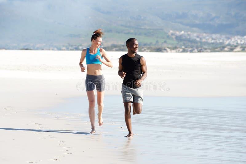 Pares jovenes felices de la raza mixta que corren en la costa foto de archivo libre de regalías