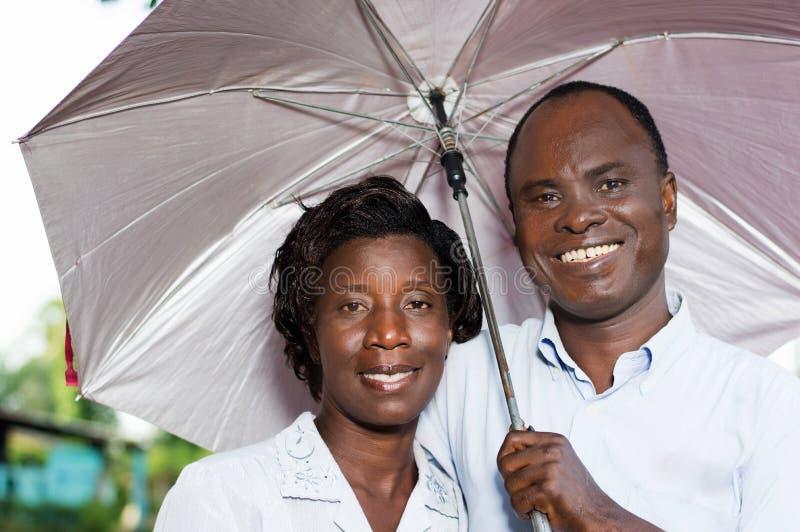 Pares jovenes felices debajo de un paraguas imágenes de archivo libres de regalías