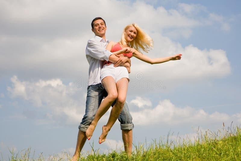 Pares jovenes felices del amor - saltando bajo el cielo fotografía de archivo libre de regalías