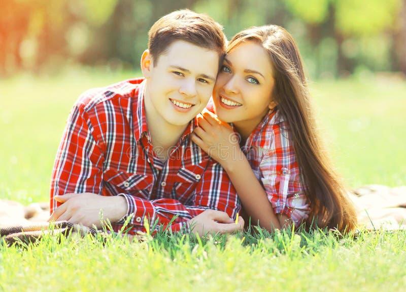 Pares jovenes felices del retrato que tienen mentira sonriente de la diversión en hierba imagenes de archivo