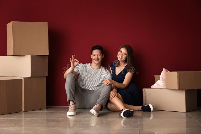 Pares jovenes felices después de mover a su nueva casa imagenes de archivo