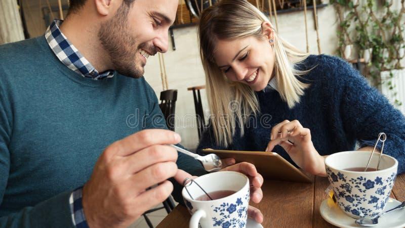 Pares jovenes felices el fecha en cafetería foto de archivo