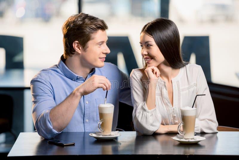 Pares jovenes felices en amor en la fecha romántica en restaurante imagenes de archivo