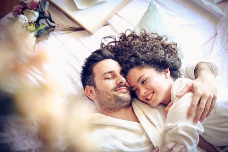 Pares jovenes felices en cama fotos de archivo libres de regalías