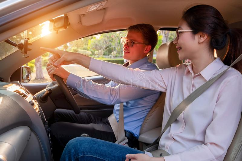 Pares jovenes felices en coche mientras que conduce un coche, conduciendo concepto del coche foto de archivo