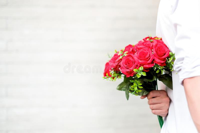 Pares jovenes felices en el amor que abraza y que sostiene rosas rojas en las manos para la sorpresa su novia, concepto de los pa foto de archivo libre de regalías