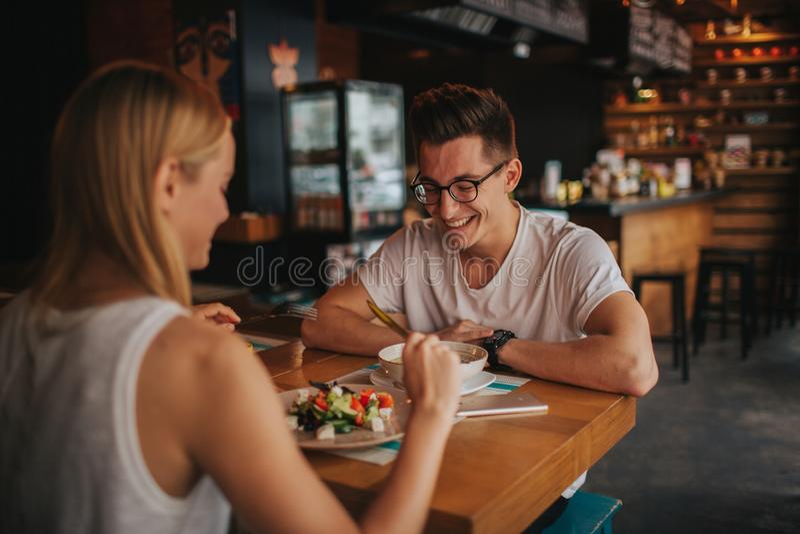 Pares jovenes felices en el amor que tiene una fecha agradable en una barra o un restaurante Ellos que cuentan algunas historias  imagen de archivo libre de regalías
