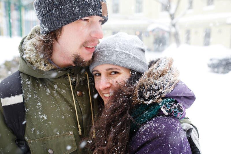 Pares jovenes felices en el día nevoso del invierno que se divierte en el fondo de la ciudad foto de archivo libre de regalías