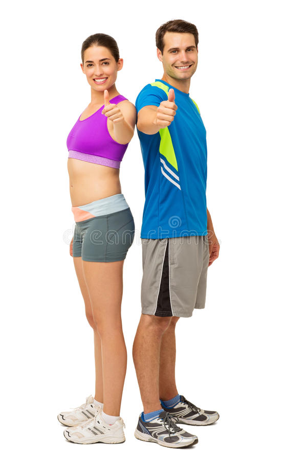 Pares jovenes felices en el desgaste de los deportes que gesticula los pulgares para arriba fotografía de archivo