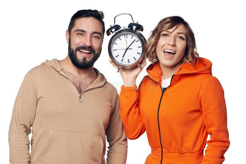 Pares jovenes felices en la ropa casera que sostiene el despertador grande foto de archivo
