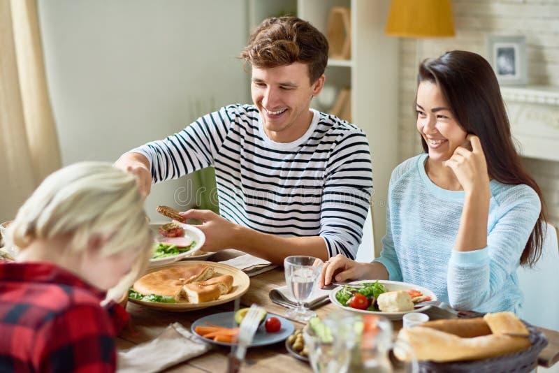Pares jovenes felices en la tabla de cena imagen de archivo