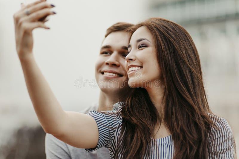 Pares jovenes felices en los amigos de los adolescentes del amor vestidos en el estilo sport que hace el selfie en la calle imagenes de archivo