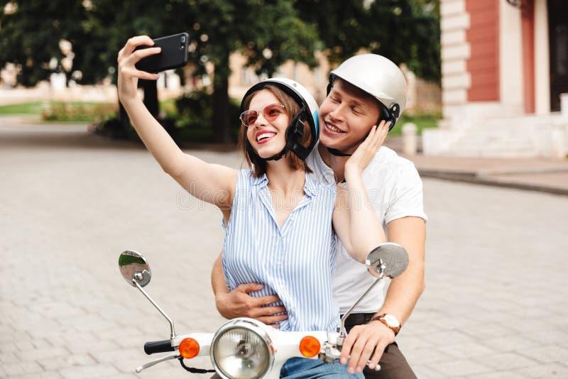 Pares jovenes felices en los cascos protectores que hacen el selfie en smartphone imagen de archivo