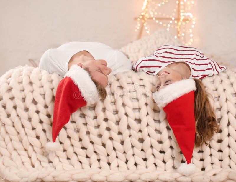 Pares jovenes felices en los sombreros de Papá Noel que se divierten en cama en casa imagenes de archivo