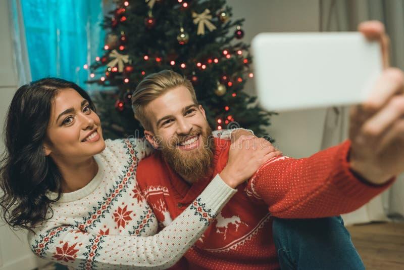 pares jovenes felices en los suéteres del invierno que toman el selfie fotografía de archivo