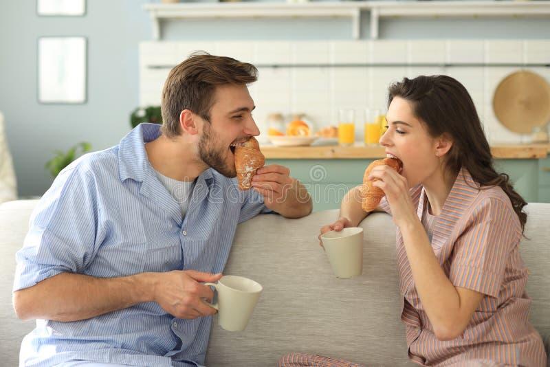 Pares jovenes felices en pijamas en la cocina que desayuna, aliment?ndose un cruas?n imagen de archivo libre de regalías