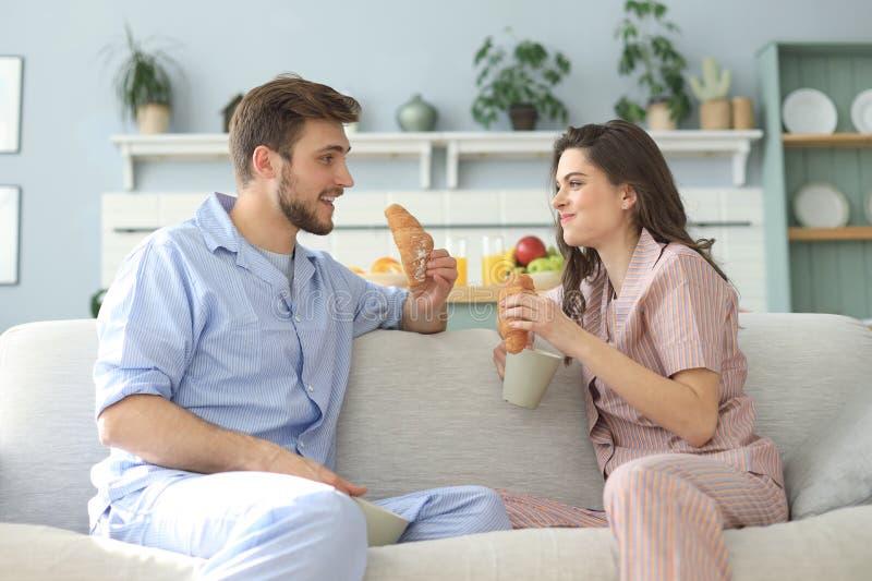 Pares jovenes felices en pijamas en la cocina que desayuna, aliment?ndose un cruas?n foto de archivo