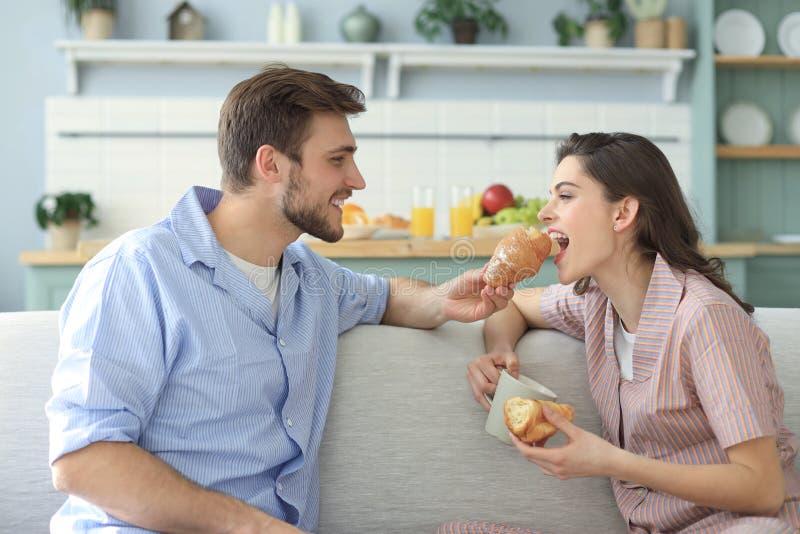 Pares jovenes felices en pijamas en la cocina que desayuna, aliment?ndose un cruas?n fotografía de archivo