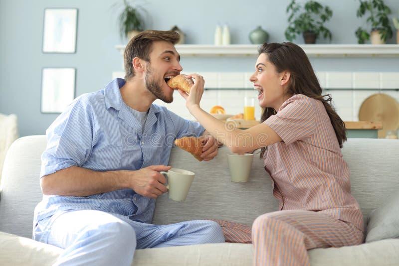 Pares jovenes felices en pijamas en la cocina que desayuna, aliment?ndose un cruas?n fotos de archivo