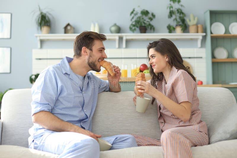Pares jovenes felices en pijamas en la cocina que desayuna, aliment?ndose un cruas?n foto de archivo libre de regalías