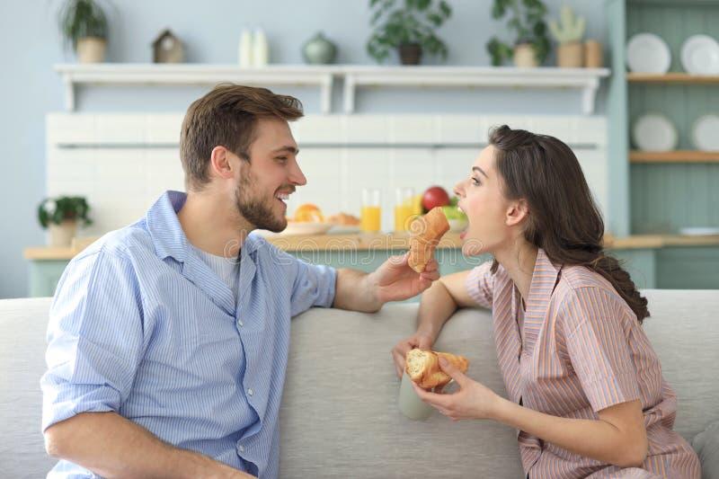 Pares jovenes felices en pijamas en la cocina que desayuna, aliment?ndose un cruas?n imágenes de archivo libres de regalías