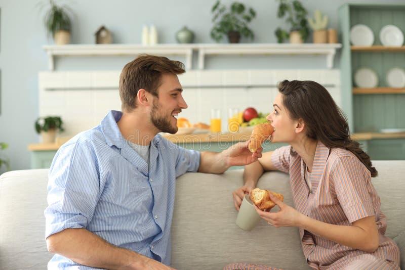 Pares jovenes felices en pijamas en la cocina que desayuna, comiéndose un cruasán imagenes de archivo