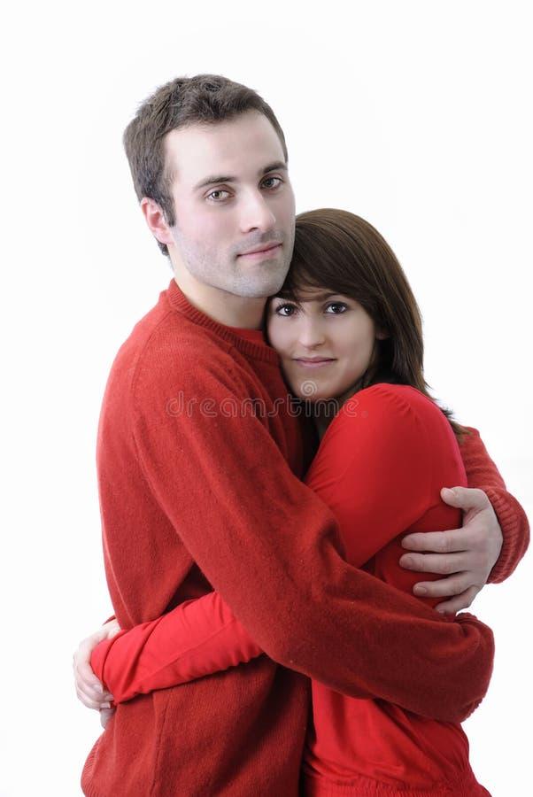 Pares jovenes felices en rojo contra el fondo blanco fotos de archivo