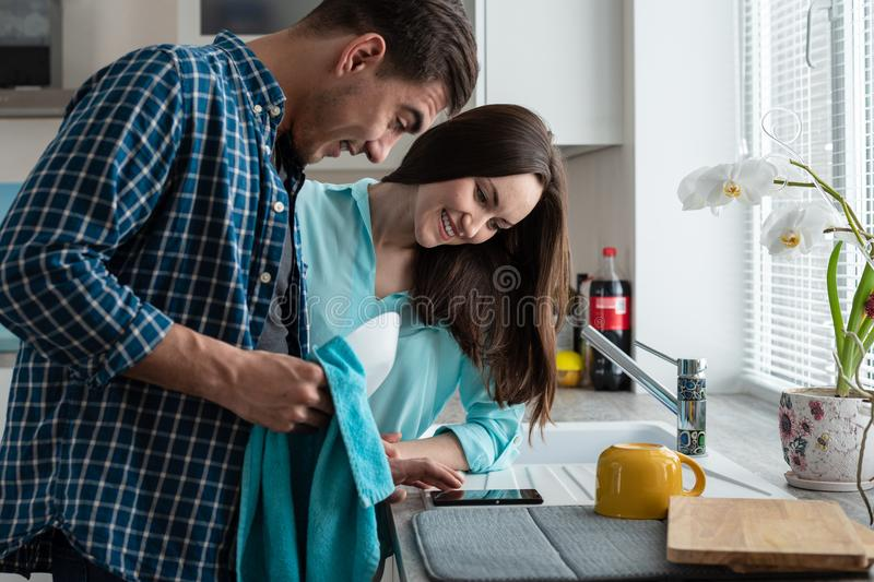 Pares jovenes felices en una cocina con los platos limpios en las manos del reloj al smartphone La visión desde el lado fotos de archivo