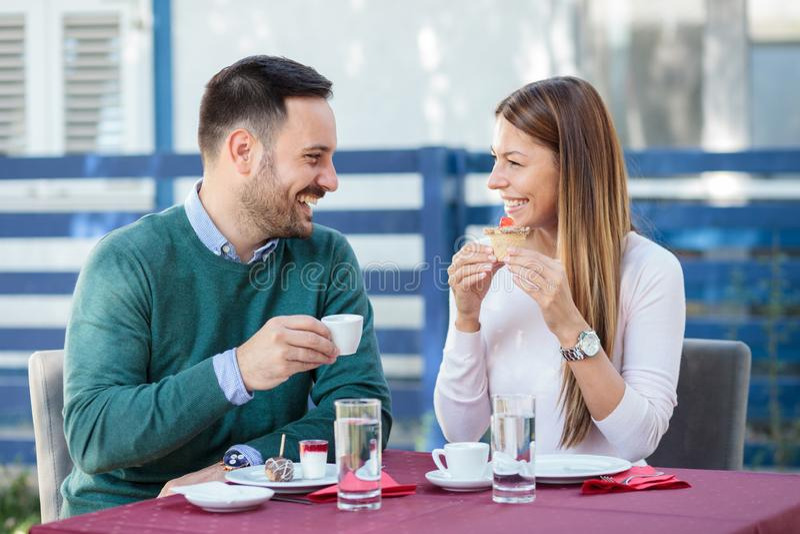 Pares jovenes felices hermosos que comen las tortas y que beben el café en un restaurante imagenes de archivo