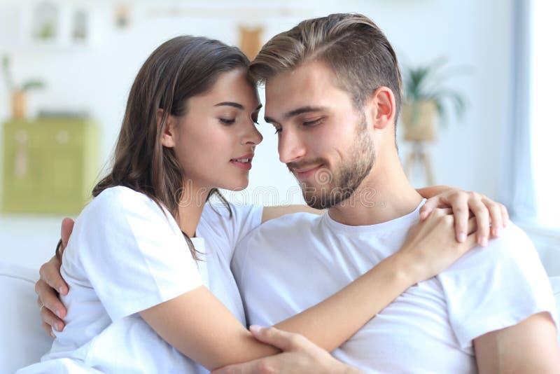 Pares jovenes felices que abrazan y que miran uno a en casa interior foto de archivo