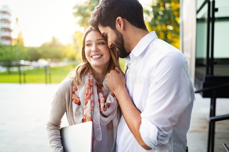 Pares jovenes felices que abrazan y que r?en al aire libre imagen de archivo libre de regalías