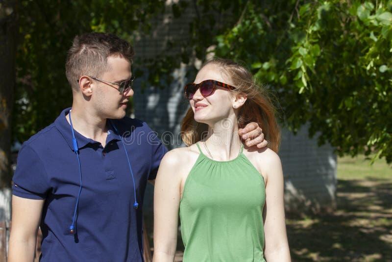 Pares jovenes felices que abrazan y que r?en al aire libre imagenes de archivo