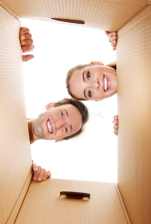 Pares jovenes felices que abren una caja del cartón y que miran dentro imágenes de archivo libres de regalías