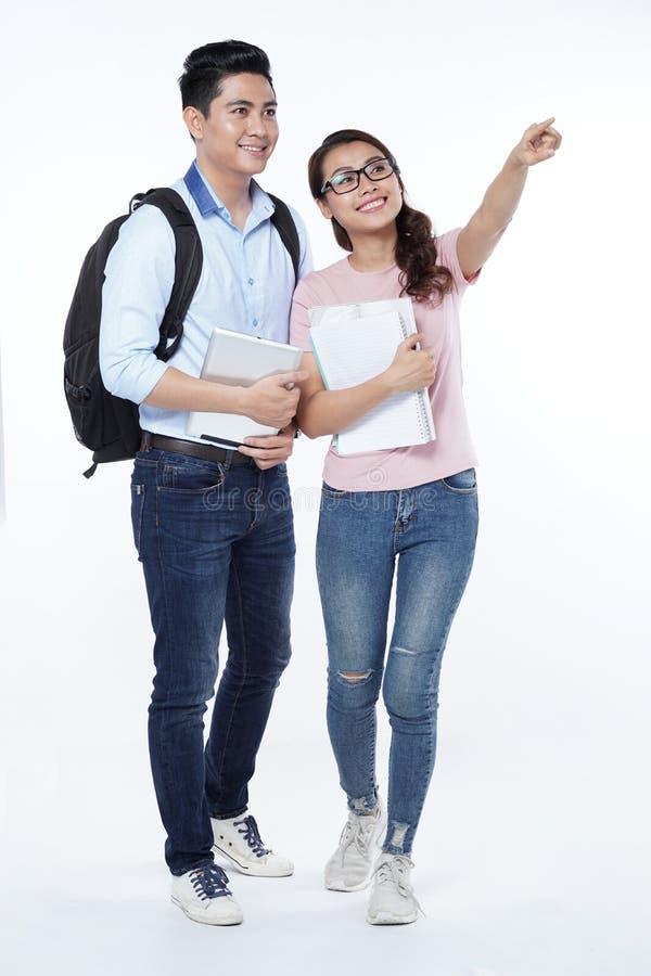 Pares jovenes felices que caminan con los libros en las manos, aisladas en el fondo blanco foto de archivo libre de regalías