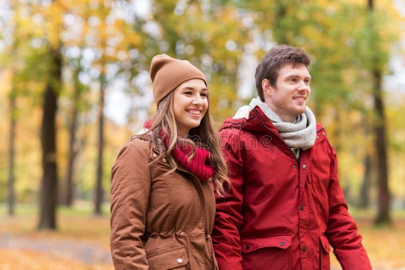 Pares jovenes felices que caminan en parque del otoño fotos de archivo libres de regalías