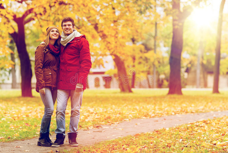 Pares jovenes felices que caminan en parque del otoño imagenes de archivo