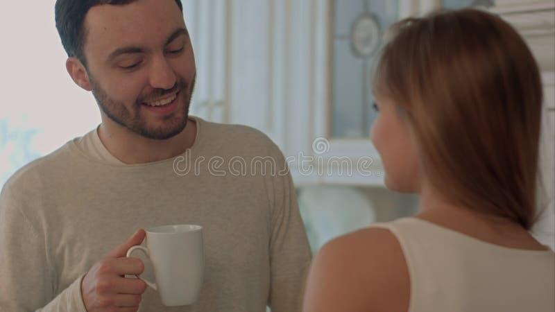 Pares jovenes felices que cocinan junto en la cocina en casa y besarse foto de archivo libre de regalías