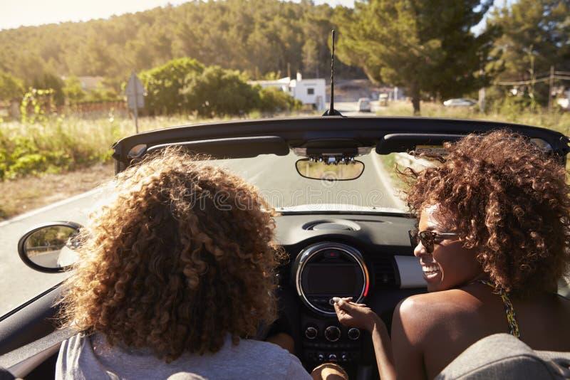Pares jovenes felices que conducen en un coche de tragante abierto, Ibiza, España imagen de archivo