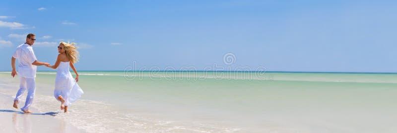 Pares jovenes felices que corren llevando a cabo las manos en una playa tropical fotos de archivo