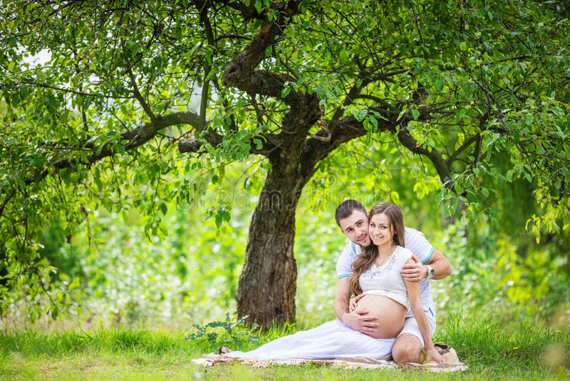 Pares jovenes felices que cuentan con al bebé, mujer embarazada con el vientre conmovedor del marido imagen de archivo