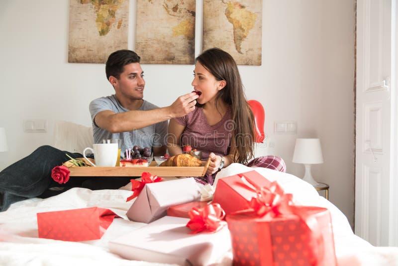Pares jovenes felices que desayunan asombrosamente en cama imagenes de archivo