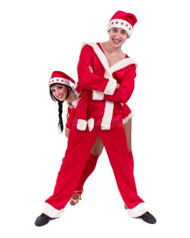 Pares jovenes felices que desgastan la ropa de Papá Noel fotografía de archivo