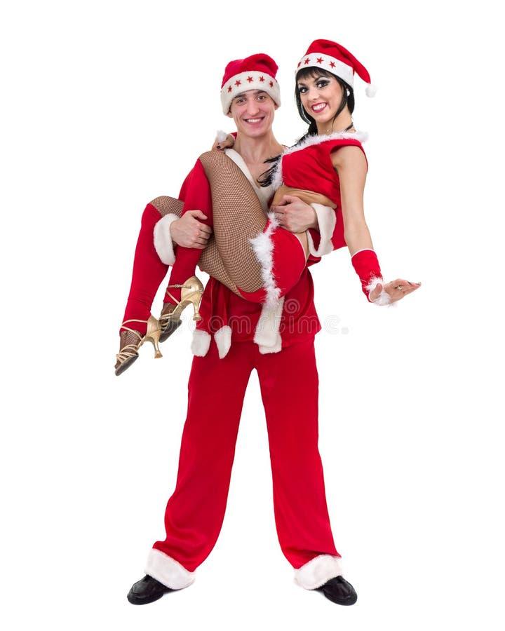 Pares jovenes felices que desgastan la ropa de Papá Noel imagen de archivo libre de regalías