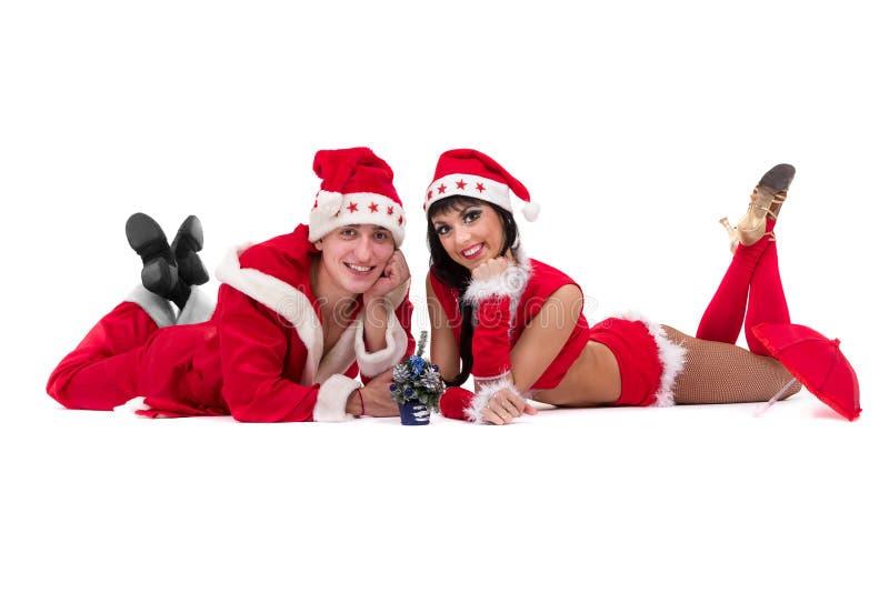 Pares jovenes felices que desgastan la ropa de Papá Noel imagenes de archivo