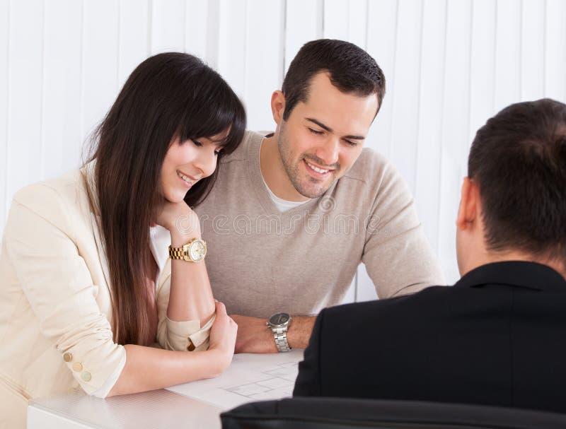 Pares jovenes felices que discuten con el consultor foto de archivo