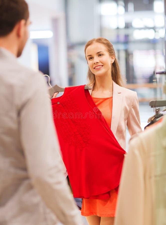 Pares jovenes felices que eligen la ropa en alameda imagen de archivo